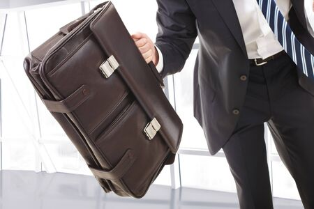Close-up of the briefcase held by running businessman photo