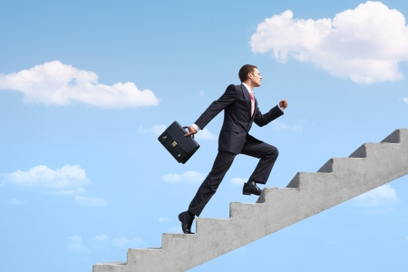 job promotion: Image of confident businessman with briefcase walking upstairs