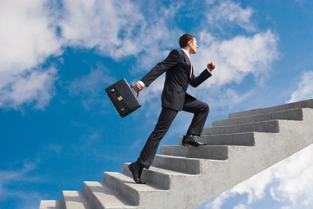 steps to success: Image of confident businessman with briefcase walking upstairs