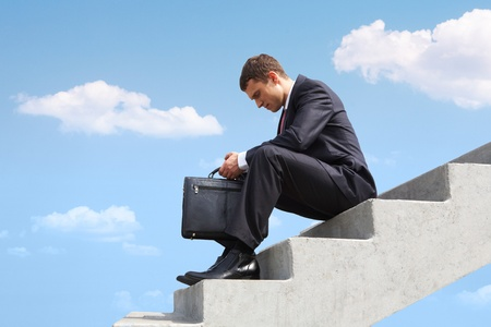 hombre preocupado: Imagen de hombre de negocios pensativo, sentado en las escaleras contra el cielo azul