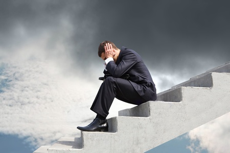 worried executive: Image of pensive businessman sitting on stairs against thunderclouds Stock Photo