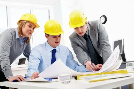 Three architects sitting at table and looking at a project photo