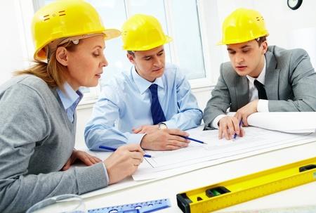 arquitecto: Tres arquitectos sentado a la mesa y discutir tr�mites Foto de archivo