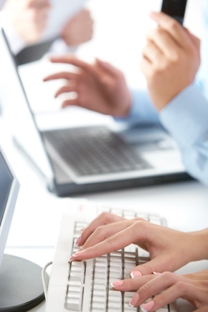 Typing female hands in office background photo