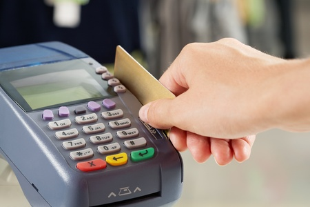 electronic store: Close-up of payment machine buttons with human hand holding plastic card near by