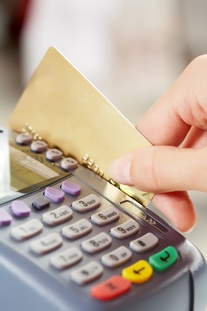 debit: Close-up of payment machine while human hand keeping plastic card in it