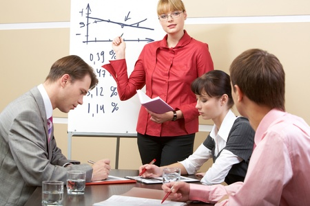 Photo of smart woman pointing at whiteboard at seminar while business partners listening to her Stock Photo - 9633281