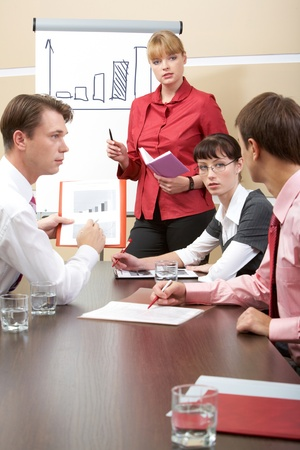 Vertical image of business team talking during meeting while confident man explaining something photo