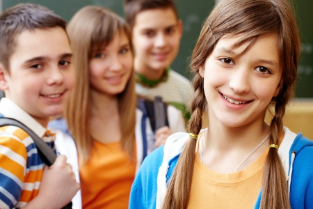 highschool: Confident student looking at camera with her friends behind Stock Photo