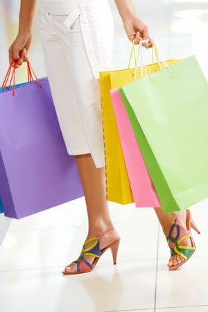 Close-up of beautiful female legs holding bags in the mall photo