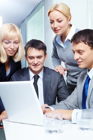 Four business people working with laptop in office Stock Photo - 9634587
