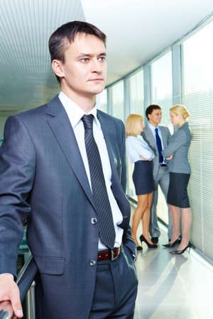 Portrait of a young confident businessman with working team on background Stock Photo - 9634111