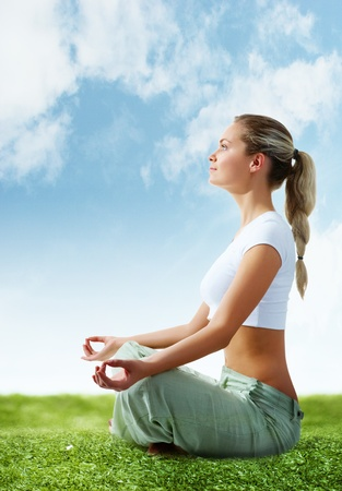 sportwear: Portrait of young woman meditating in pose of lotus on green grass