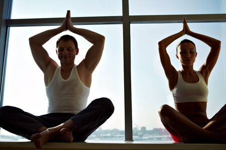 Photo of meditating people sitting with their arms raised and kept in touch photo