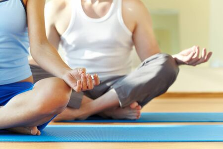 position: Close-up of feminine and masculine arms and crossed legs during meditation Stock Photo