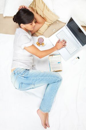 A young girl working on computer in bed Stock Photo - 9633516