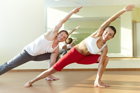 растягивание: Image of young sporty girl and guy doing physical exercise