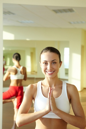 Portrait of smiling girl doing physical exercises and looking at camera photo