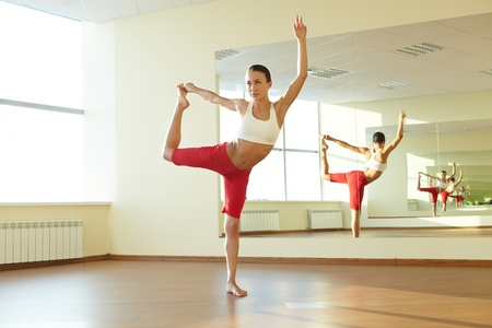 back exercise: Portrait of young sporty girl doing physical exercise in front of mirror Stock Photo