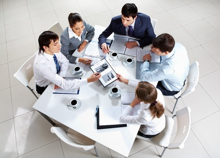 team strategy: Above view of business team sitting around table and working with papers