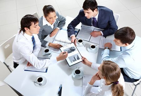 consulting team: Above view of business team sitting around table and working with papers