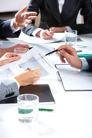 show business: Photo of businesspeople�s hands holding papers and pens over workplace