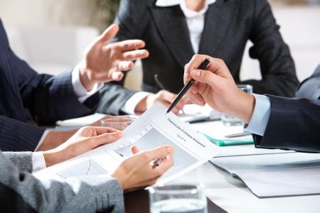 Close-up van de zakenman uit te leggen een financieel plan aan collega's op de bijeenkomst