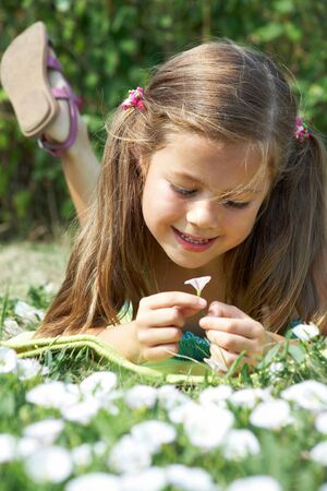Close-up of girl lying on green grass and enjoying nice smell of tiny flower photo