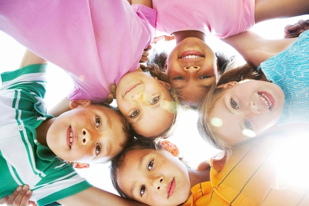 girl child: Below view of happy children embracing each other and smiling at camera