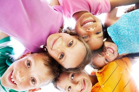 ni�os contentos: Por debajo de la vista de los ni�os felices abrazados y sonriendo a la c�mara