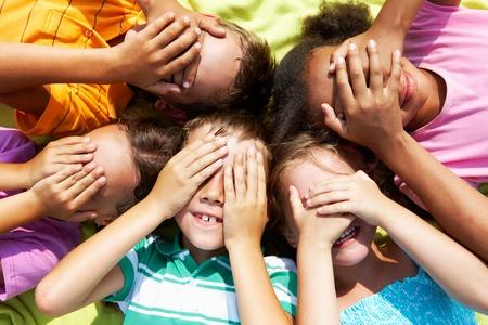 eyes closing: Retrato de ni�os en edad preescolar felices mintiendo y cerrar de ojos por manos