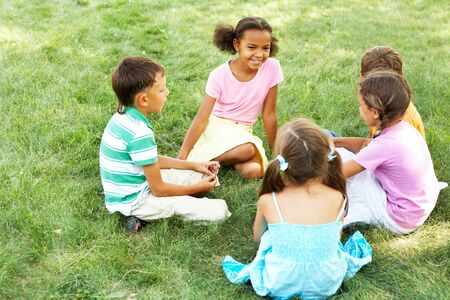 people interacting: Portrait of cute kids seated on green grass and chatting Stock Photo