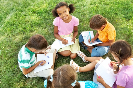 Portrait of cute kids seated on green grass with copybooks and pencils photo