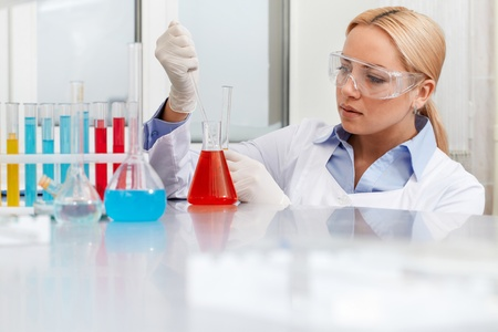 clinician: Serious clinician looking at flask with liquid in laboratory