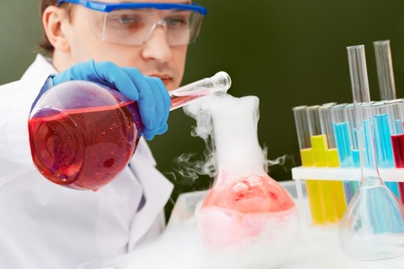 Young clinician making experiment with steaming liquid in laboratory photo