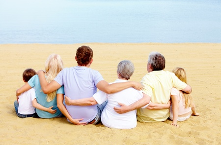 Backs of serene family members sitting on sandy shore in front of blue water photo
