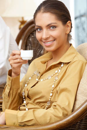 Portrait of elegant business lady with cup of coffee in hands looking at camera photo