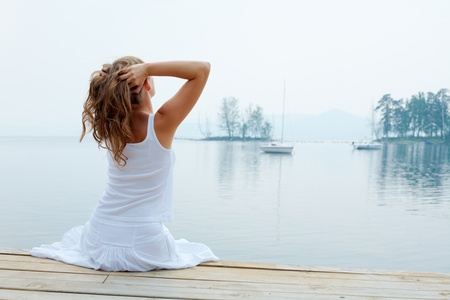 Rear view of pretty young lady in white cotton clothes having rest by the seaside photo