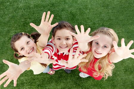 Image of happy friends on the grass raising arms  photo