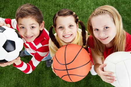 youth sports: Image of happy friends on the grass with balls looking at camera  Stock Photo