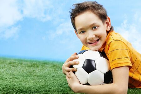 Image of happy boy lying on the grass with ball and looking at camera  Stock Photo - 9634279