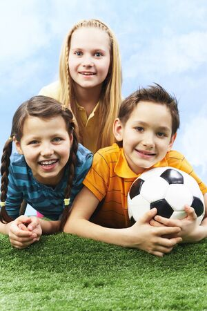 Image of happy friends lying on the grass with ball and looking at camera Stock Photo - 9635101