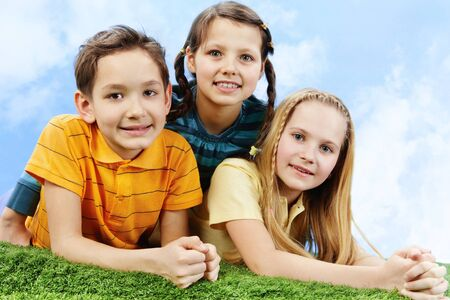 the three sisters: Image of happy friends lying on the grass and looking at camera