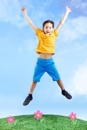 boy jumping: Imagen de ni�o feliz saltando sobre la hierba y mirando a la c�mara  Foto de archivo