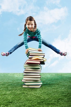 Image of happy girl jumping on the grass through stack of books photo