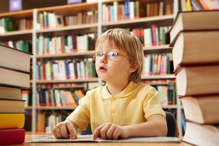 interested: Portrait of interested schoolkid reading book in the library Stock Photo