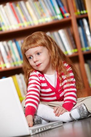 Portrait de jeune fille intelligente, assis sur le sol en bibliothèque devant un ordinateur portable Banque d'images