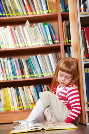 educational: Portrait of smart girl sitting on the floor in library with open book in front Stock Photo