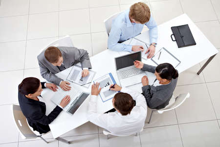 Above view of business team sitting around table and working photo