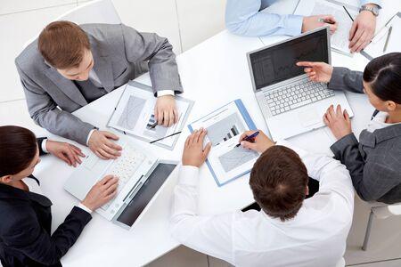 reuniones empresariales: Por encima de la vista del equipo de negocios sentados alrededor de tabla y trabajo